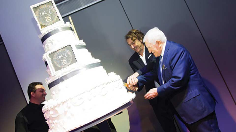 Alain Milgrom and his father Salomon cut the cake at the Sol's anniversary party